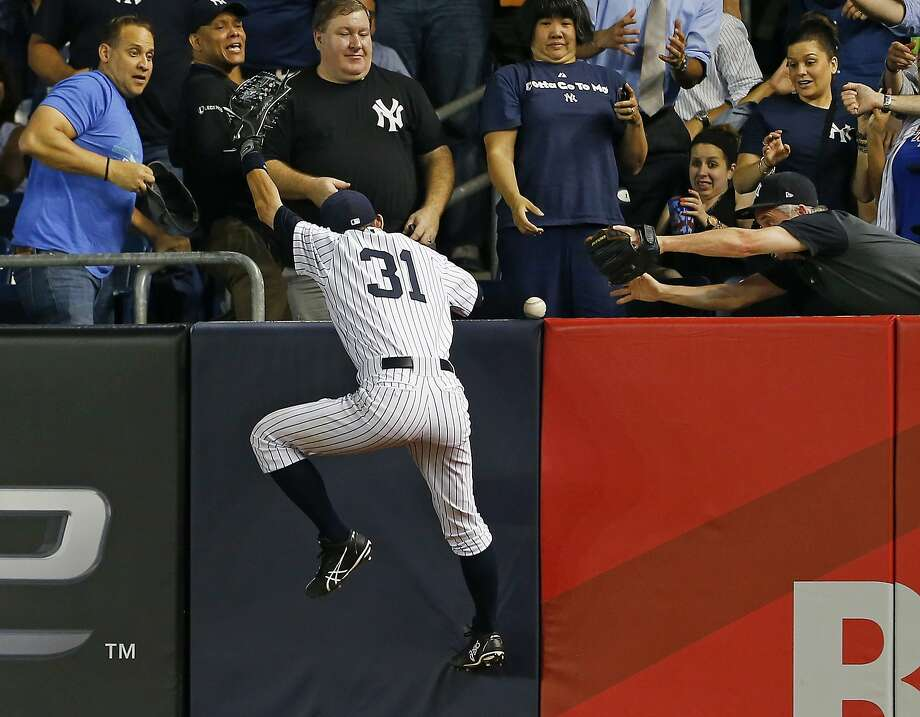 Ichiro Suzuki climbs the wall in right field attempting to catch Yoenis Céspedes' second home run of the game. Photo: Rich Schultz, Getty Images