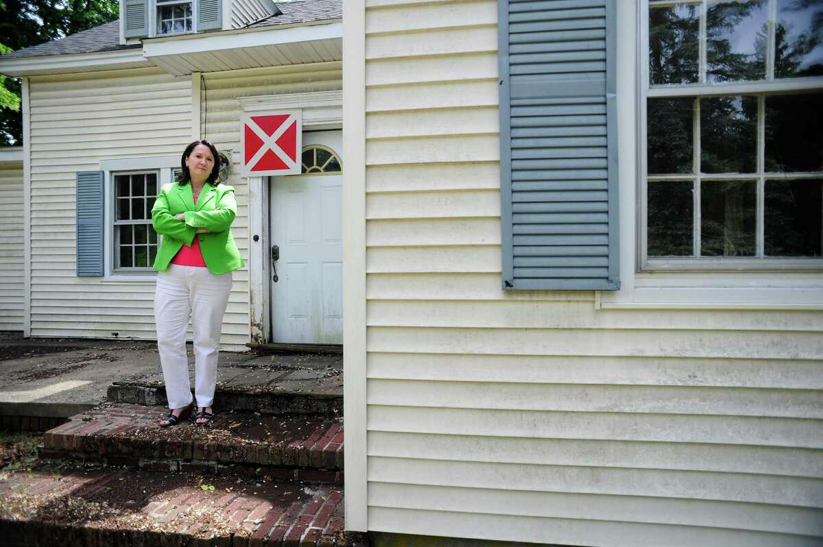 Niskayuna Town Board member Denise Murphy McGraw stands on the front porch of an empty building at the corner of Balltown Road and Union Street on Wednesday, June 4, 2014, in Schenectady, N.Y. The white and red X sign was put up by the city to mark the building as empty. (Paul Buckowski / Times Union)