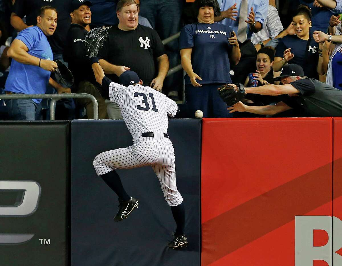 NEW YORK, NY - JUNE 4: Ichiro Suzuki #31 of the New York Yankees climbs the wall in right field in an attempt to catch a ball that was hit for a home run by Yoenis Cespedes #52 of the Oakland Athletics during the sixth inning in a MLB baseball game at Yankee Stadium on June 4, 2014 in the Bronx borough of New York City. (Photo by Rich Schultz/Getty Images) ORG XMIT: 477584351