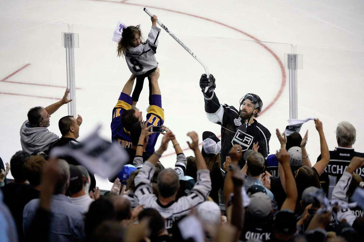 The Kings' Justin Williams gives his stick to a young fan after scoring the game-winning goal.