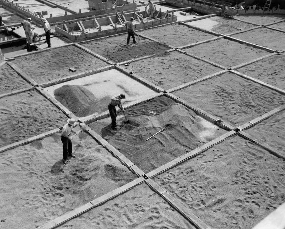 August 11, 1954- Workmen spread coarse gravel between forms on floor of graving dock. With sand added gravel will form greasy surface so pier structure will skid out of dock easily on the 1st Avenue South Bridge. Photo by Miller. Photo: FILE PHOTO, SEATTLEPI.COM / SEATTLEPI.COM