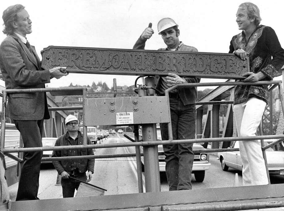 October 27, 1973 - Roy Ruden, City Engineering Dept. worker, center, signaled 'up' to the truck driver as they attach the Fremont Bridge sign. Photo by Phil Webber. Photo: FILE PHOTO, SEATTLEPI.COM / SEATTLEPI.COM
