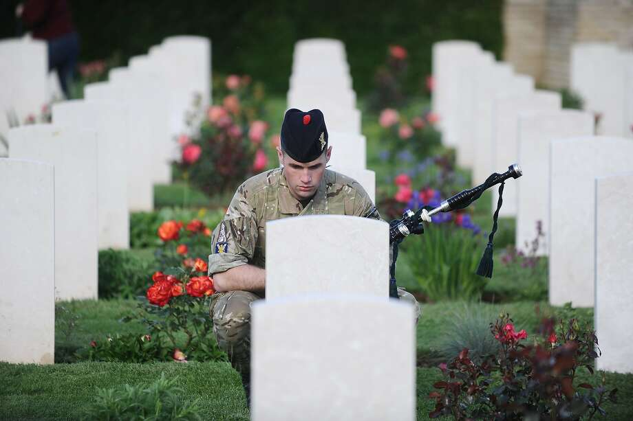 A British soldier pays his respects as he visits a military cemetery on June 4, 2014 in Ranville, northwestern France. The D-Day ceremonies on June 6 this year mark the 70th anniversary since the launch of the vast military operation by Allied forces in Normandy, which turned the tide of World War II, eventually leading to the liberation of occupied France and the end of the war against Nazi Germany. TOPSHOTS/AFP PHOTO / JEAN-SEBASTIEN EVRARDJEAN-SEBASTIEN EVRARD/AFP/Getty Images Photo: Jean-sebastien Evrard, AFP/Getty Images