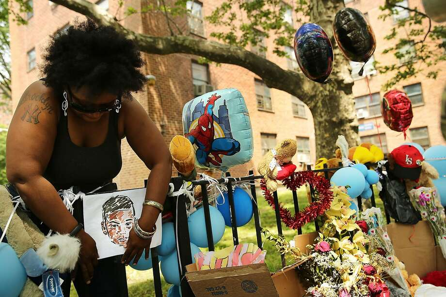 NEW YORK, NY - JUNE 04:  Luwana Staley hangs up a portrait of Prince Joshua Avitto, 6, who was killed last Sunday in an East New York neighborhood apartment building elevator on June 4, 2014 in the Brooklyn borough of New York City. Prince Joshua Avitto, 6, and Mikayala Capers, 7, were stabbed repeatedly by a man who later fled the scene and is still at large. Joshua died at Brookdale Hospital while Capers is in critical condition after undergoing surgery. It is believed that the suspect may have been involved with another recent stabbing in the same neighborhood.  (Photo by Spencer Platt/Getty Images) Photo: Spencer Platt, Getty Images