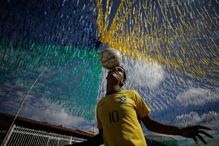 Joao Paulo, 16, plays ball in the street decorated for the upcoming World Cup in the Ceilandia suburb of Brasilia, Brazil, Wednesday, June 4, 2014. The international soccer tournament is set to begin next week. (AP Photo/Eraldo Peres) Photo: Eraldo Peres, Associated Press