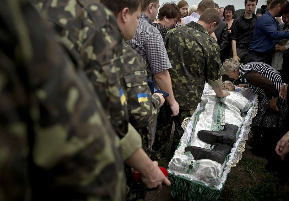 Pro-Russian rebels and relatives walk next to the coffin of Alexander Alexandrovich Gizai, a member of military-patriotic group 'Kaskad' who was killed Monday during clashes with Ukrainian troops, during his funeral in Luhansk, eastern Ukraine, Wednesday, June 4, 2014. (AP Photo/Vadim Ghirda) Photo: Vadim Ghirda, Associated Press