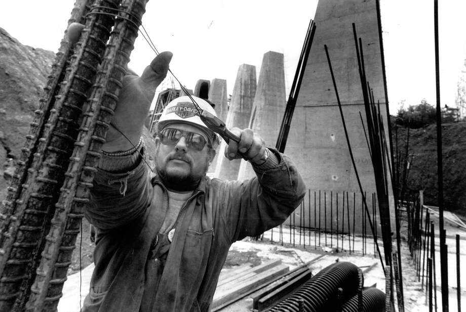 April 8, 1991 - Butch Arens, an Iron Worker for Triune Steel, Inc., ties rebar together before plywood forms are made and cement poured at an approach to the Lacey V. Murrow replacement span. Photo by Grant Haller.. Photo: FILE PHOTO, SEATTLEPI.COM / SEATTLEPI.COM
