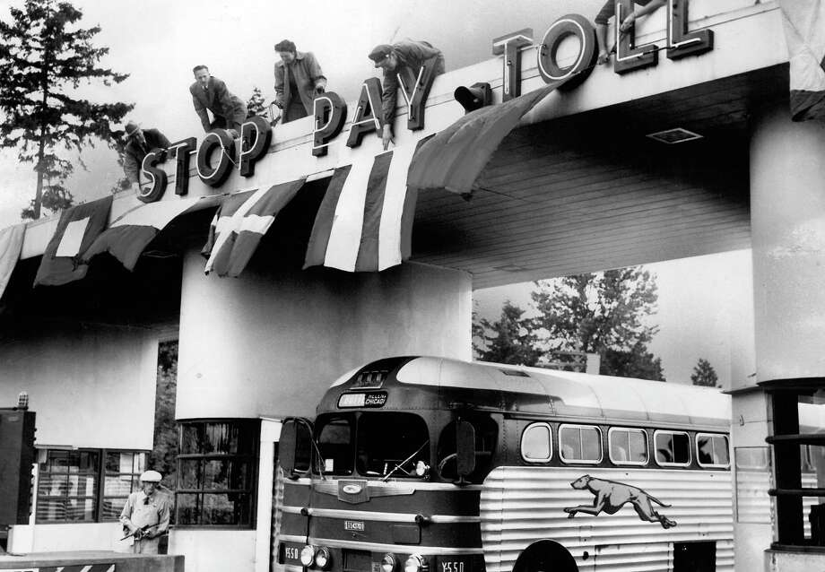 July 2, 1949 - Putting up flags on the Lake Washington Floating Bridge toll plaza area in preparation for end-of-toll-ceremonies. Photo: FILE PHOTO, SEATTLEPI.COM / SEATTLEPI.COM