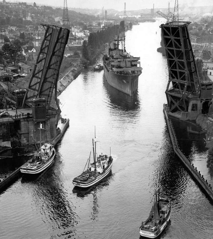 May 21, 1946 - Navy troopship which went askew while trying to thread between piers of Fremont Bridge is shown at anchor while tug prepares to help her through. Photo: FILE PHOTO, SEATTLEPI.COM / SEATTLEPI.COM