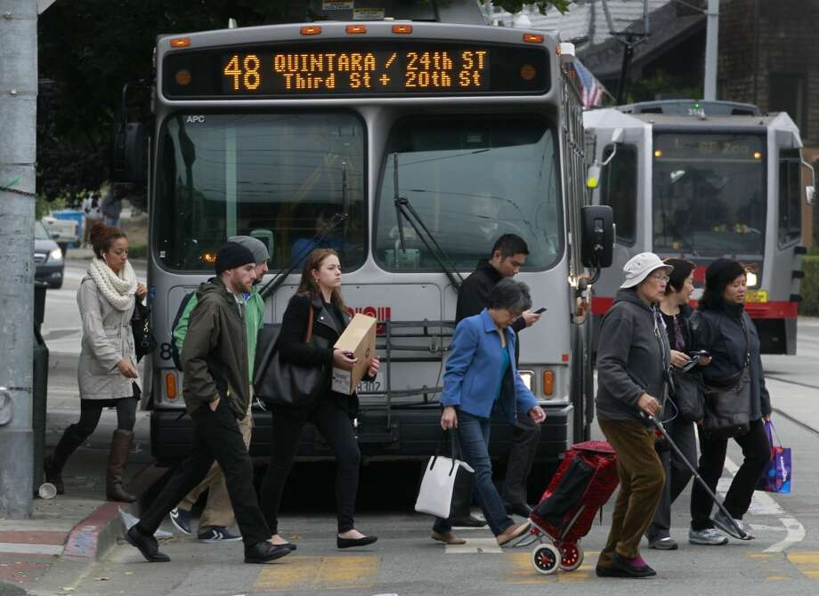 Muni passengers cross the street to the West Portal Metro station on the third day of a sickout by transit employees in San Francisco, Calif. on Wednesday, June 4, 2014. More workers reported for work today, but the system is still not operating at full capacity. The union employees are upset by a contract proposal made by MTA management. Photo: Paul Chinn, The Chronicle