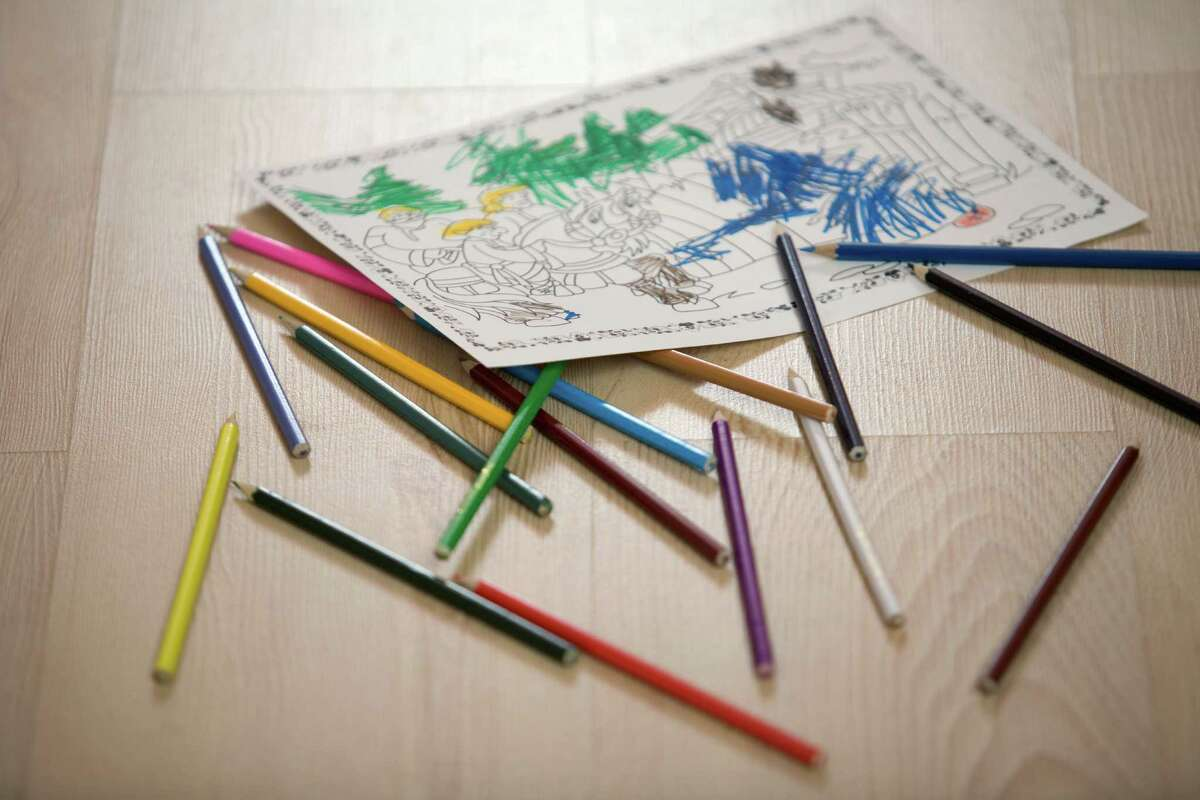 A coloring book page and colored pencils.