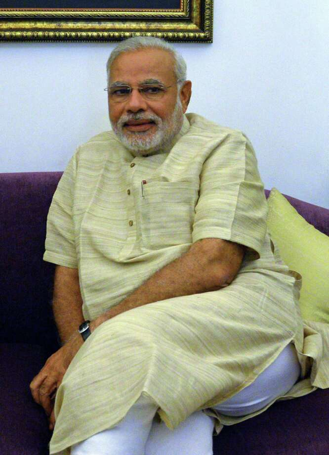 Newly elected Indian prime minister Narendra Modi has made headlines and started a fashion trend by wearing his unique take on a traditional Indian kurta, left. He also created a stir when he wore a more formal, long-sleeve, button-cuffed version at his swearing-in ceremony. Photo: RAVEENDRAN, Staff / AFP