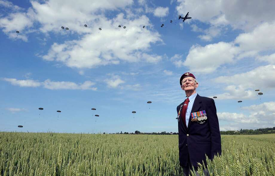 D-Day memories: British World War II veteran Frederick Glover poses for a photograph as soldiers parachute down 