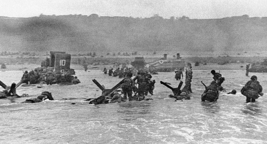 FILE - In this June 6, 1944 file picture, some of the first assault troops to hit the Normandy, France beachhead take cover behind enemy obstacles to fire on German forces as others follow the first tanks plunging through the water towards the German-held shore during World War II. (AP Photo) Photo: ST / AP1944
