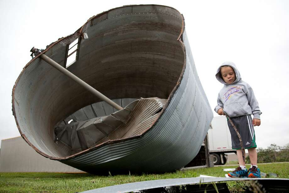 Bent bin: Four-year-old Lane Loftis examines a rumpled grain bin after a severe windstorm blew through Craig, Neb. Photo: Julia Nagy, Associated Press