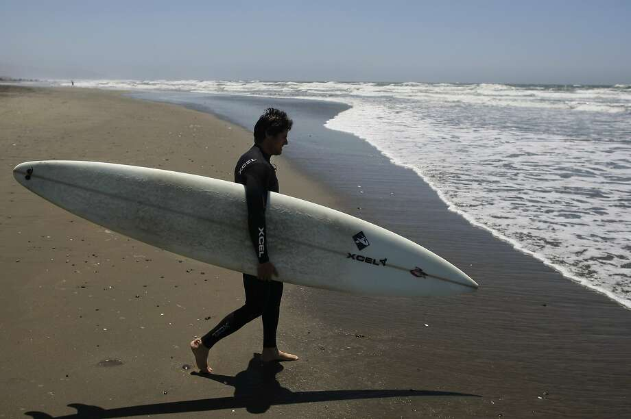 Alex Martins makes his way to the water at Ocean Beach in San Francisco, Calif. on Tuesday, May 27, 2014. The Brazilian native has surfed Mavericks and also runs a repair shop. Photo: James Tensuan, The Chronicle