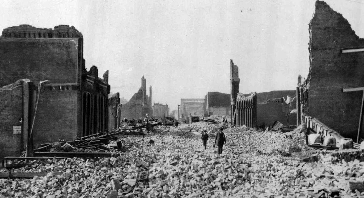 """People walk through the rubble following an earthquake in San Francisco in this April 18, 1906 file photo. On April 17, 1906, San Francisco was cosmopolitan enough to host Enrico Caruso in """"Carmen"""" and so financially flushed it ranked fourth among American cities in raising money to help victims of a volcano in Italy. A day later, San Francisco was pleading for help itself after a giant earthquake struck along the San Andreas fault. (AP Photo/File)"""