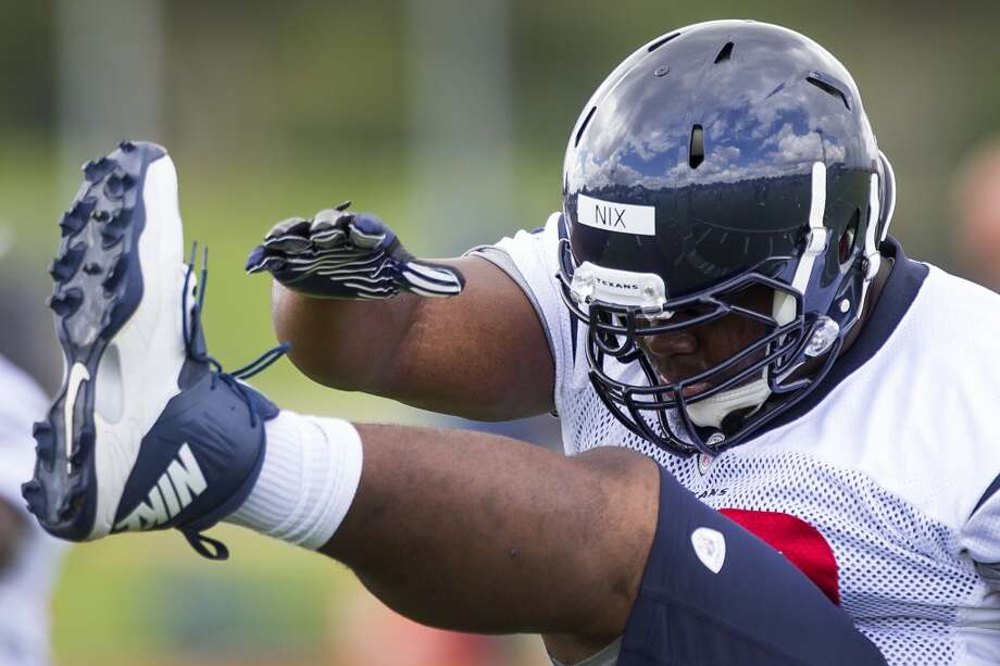 Nose tackle Louis Nix III stretches at the beginning of practice. Photo: Brett Coomer, Houston Chronicle