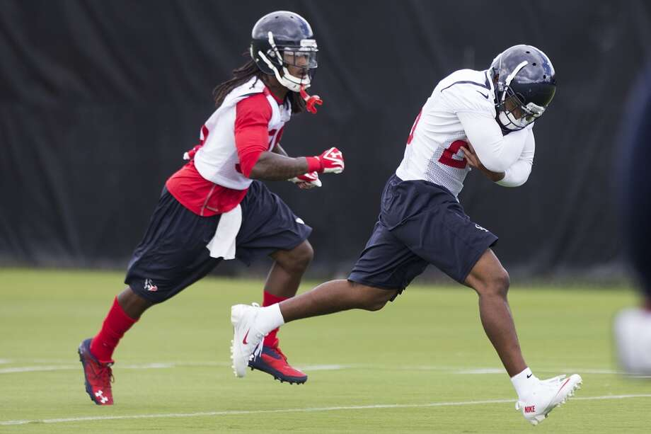 Defensive backs D.J. Swearinger, left, and Kareem Jackson run downfield after Jackson made a catch. Photo: Brett Coomer, Houston Chronicle