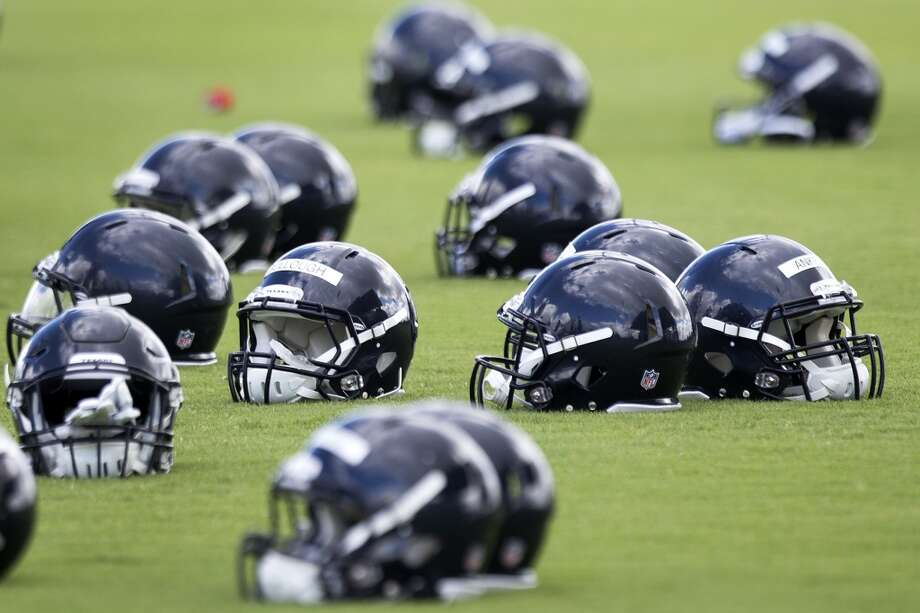 Helmets sit on the field before practice. Photo: Brett Coomer, Houston Chronicle