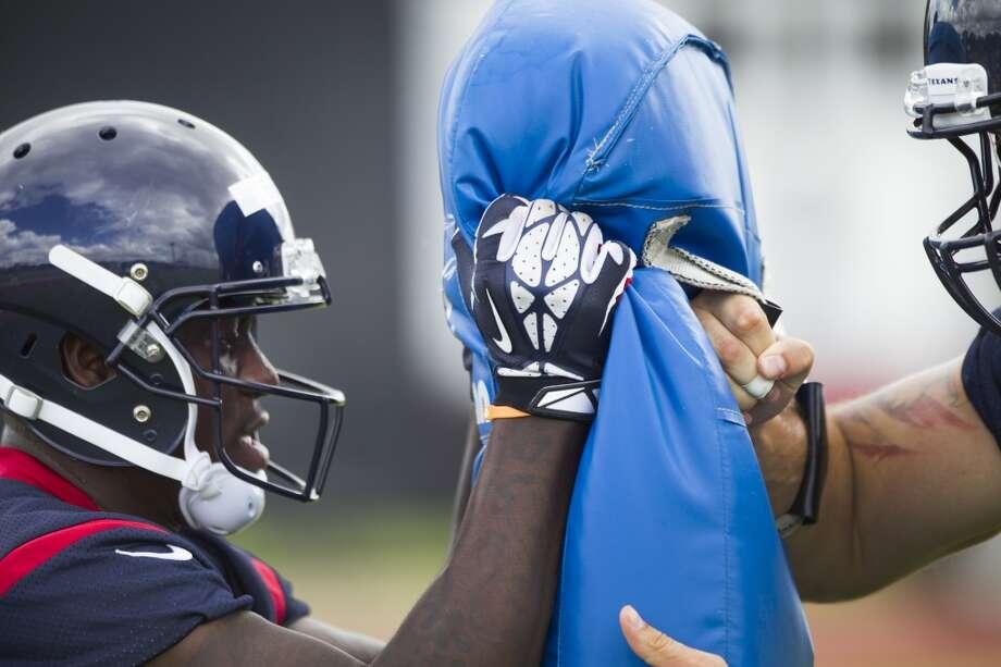 Tight end Anthony Denham hits a blocking pad. Photo: Brett Coomer, Houston Chronicle