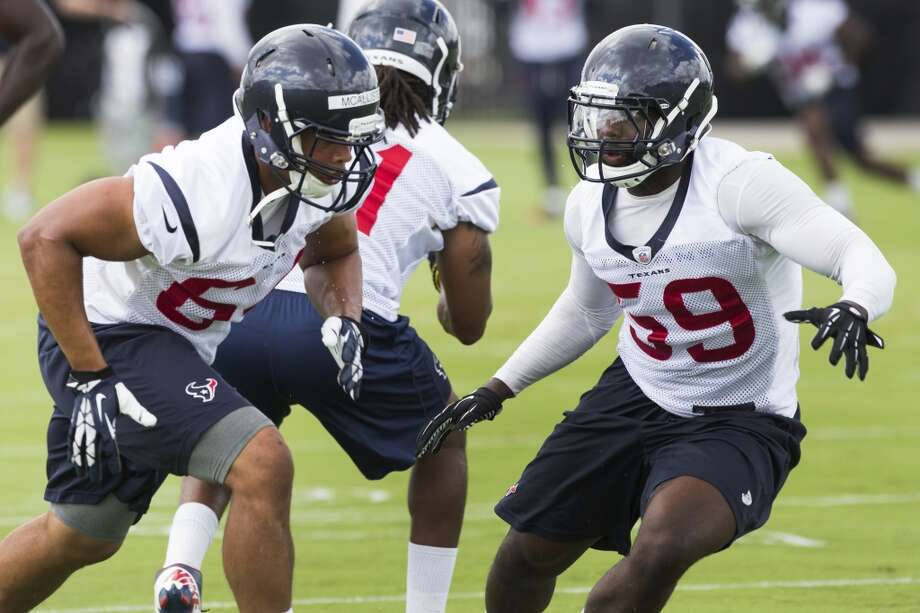 Linebackers Chris McAllister (64) and Whitney Mercilus (59) run through a drill. Photo: Brett Coomer, Houston Chronicle