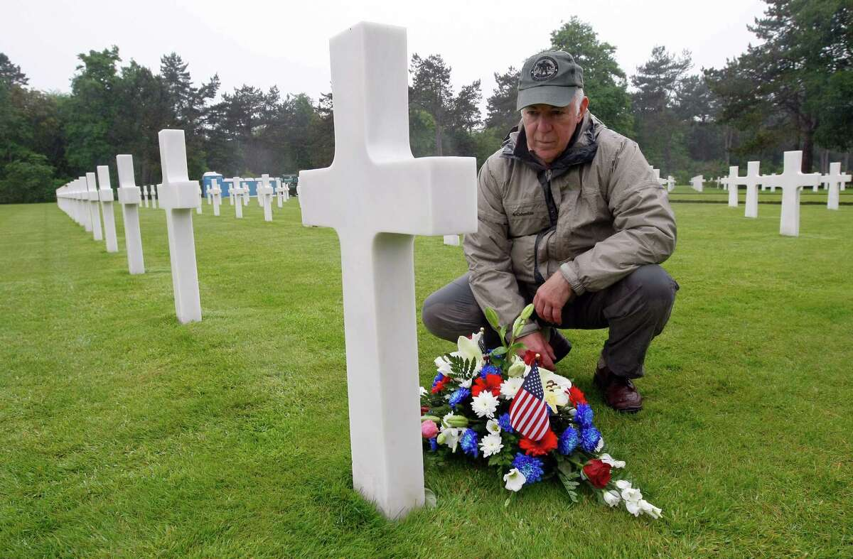 Paul Clifford, 70, from Boston MA, USA, places flowers on the grave of Walter J. Gunther Jr, the uncle of his best friend, in the Normandy American Cemetery and Memorial, in Colleville sur Mer, France, Wednesday June 4, 2014. World leaders and veterans prepare to mark the 70th anniversary of the D-Day invasion this week in Normandy.