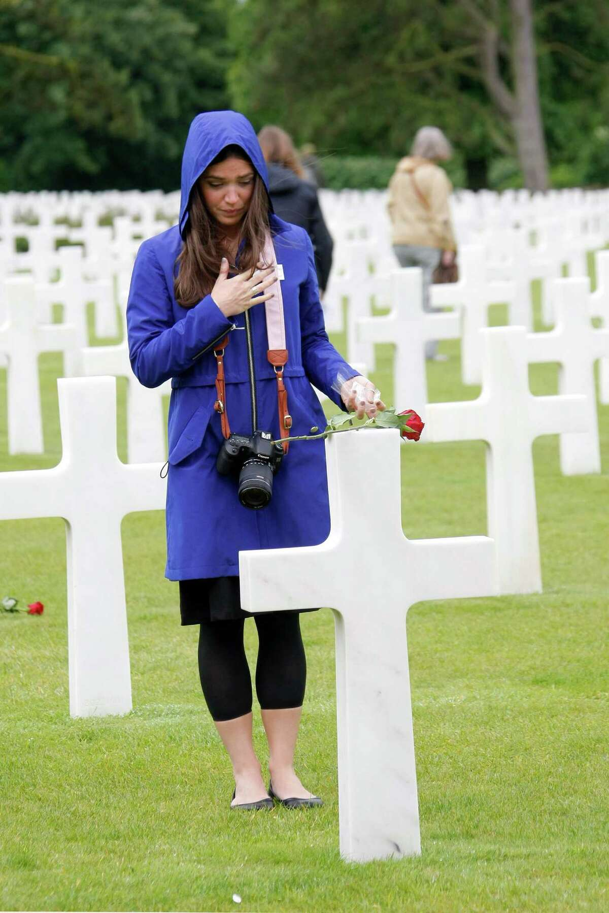 Marissa Neitling, 30, from Lake Oswego, Oregon, places a flower on a grave in the Normandy American Cemetery and Memorial, in Colleville sur Mer, France, Wednesday June 4, 2014. World leaders and veterans prepare to mark the 70th anniversary of the invasion this week in Normandy.