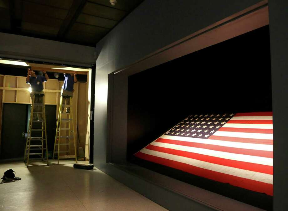In this photo taken Wednesday, May 21, 2014, workers at the Houston Museum of Natural Science work on an exhibit spotlighting the flag from the USS Texas in Houston. The 17-by-9 foot, 48-star flag flew over the battleship on D-Day, June 6, 1944, off the beaches at Normandy. Photo: Pat Sullivan, AP / AP