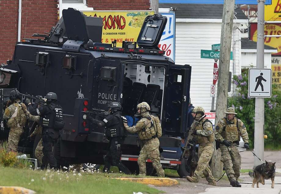 Emergency response officers enter a residence in Moncton, New Brunswick, searching for the suspect who killed three Royal Canadian Mounted Police officers in a shooting the day before. Photo: Andrew Vaughan, Associated Press