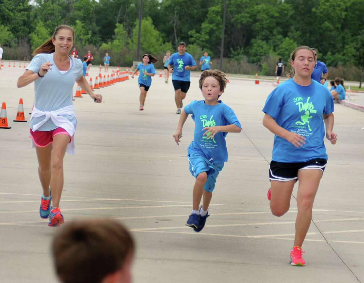 David Elementary School second grade teacher Renee Williams races her student, Mason Scott, and daughter, Erin, to the finish line during the 21st Annual David's Dream Run at the Woodforest Bank Stadium in Shenandoah. Money raised by the Dream Run benefits the David Center at Texas Children's Hospital. Over 900 runners participated in the event. Photo by David Hopper