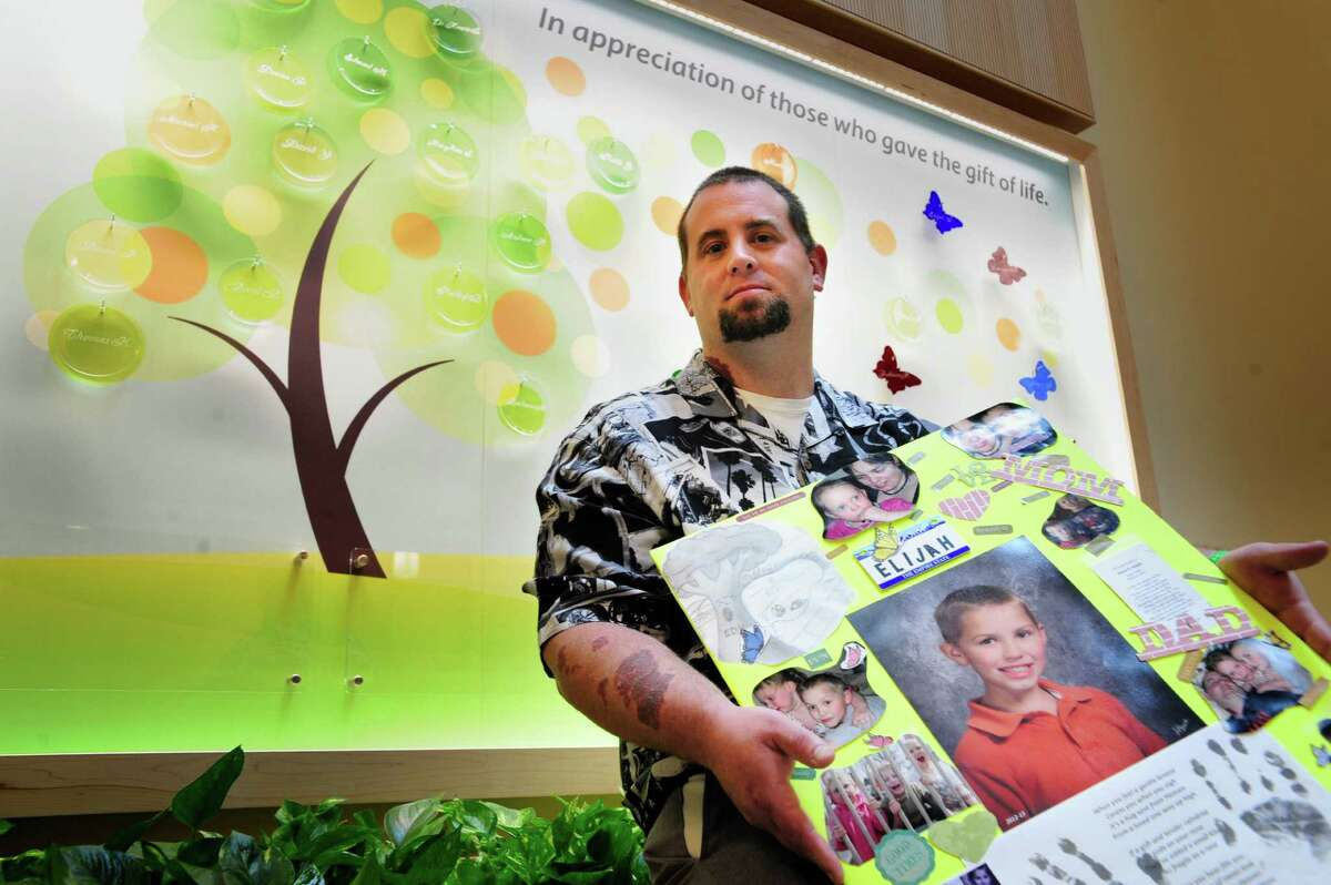 Christopher Sleight of Ballston Spa holds a photo of his son, Elijah, who was killed in a traffic accident in March of 2013 and became an organ donor. Sleight sits in front of the Tree of Life in the lobby of the Albany Medical Center on Thursday, June 5, 2014, in Albany, N.Y. The Tree of Life is dedicated to 24 individuals, including Elijah, who were organ donors in 2013 and contains glass ornaments etched with their names. Next year, the glass ornaments will be given to family members and the organ donors' names will be etched onto the bottom panel and new glass ornaments bearing the names of the current year's donors will go up on the tree. (Paul Buckowski / Times Union)