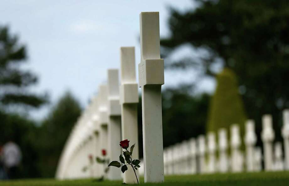 A  rose decorates the headstone of an American soldier at  Normandy American Cemetery near Omaha Beach, France. Friday is the 70th anniversary of D-Day. Photo: Win McNamee / Getty Images / 2014 Getty Images