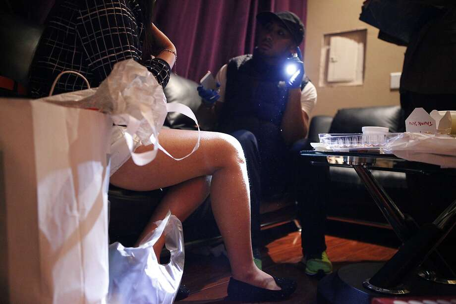 A female worker sits on a couch in an employee room while being questioned by Allan Pera of the Dept. of Public Health during a surprise inspection of the Nirvana Healthcare Center massage parlor in San Francisco on March 14, 2014.  Photo: Michael Short, The Chronicle