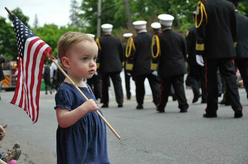 rooke Marguerite Meilhede, 2, of Queensbury pays tribute at the Glens Falls Memorial Day Parade to a