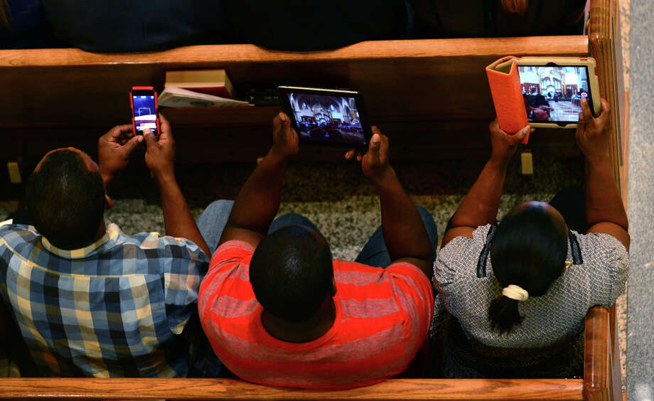 Families use smart phones and iPads to catch every moment, during Kolbe Cathedral's Class of 2014 Commencement Exercises at St. Augustine Cathedral in Bridgeport, Conn. on Thursday June 5, 2014. Photo: Christian Abraham / Connecticut Post