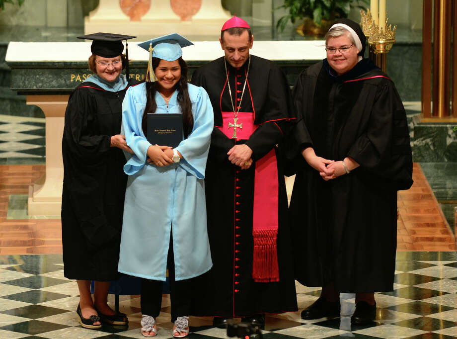 Graduate Fanny Santiago poses for a photo after receiving her diploma from Bishop Frank Caggiano, center, during Kolbe Cathedral's Class of 2014 Commencement Exercises at St. Augustine Cathedral in Bridgeport, Conn. on Thursday June 5, 2014. At left is Jo-Anne Jakab and at right is Sister Mary Grace Walsh. Photo: Christian Abraham / Connecticut Post