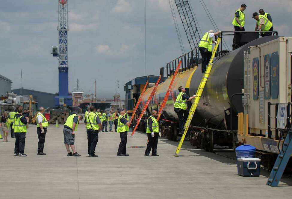 Albany first responders climb aboard a DOT-105 tanker train car to better learn how to extinguish an explosive tanker train car fire Wednesday, June 5, 2014, at the Port of Albany in Albany, N.Y. Railroad company CSX brought a ?rolling classroom? into the Port of Albany to teach local fire and emergency crews how to handle the tanker cars that are handling the surge of Bakken crude. (Tom Brenner/ Special to the Times Union)