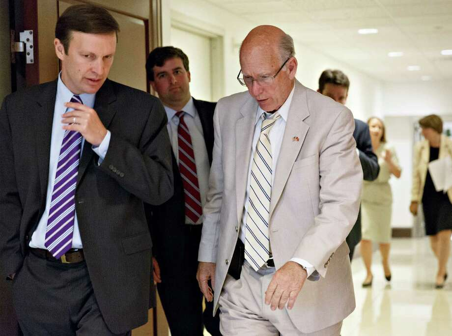 Sen. Chris Murphy, D-Conn., left, confers with Sen. Pat Roberts, R-Kan., as they join other senators for a closed-door briefing with intelligence officials about the Obama administration's decision to swap five members of the Taliban for captive Army Sgt. Bowe Bergdahl, at the Capitol in Washington, Wednesday, June 4, 2014.  (AP Photo/J. Scott Applewhite) ORG XMIT: DCSA126 Photo: J. Scott Applewhite / AP
