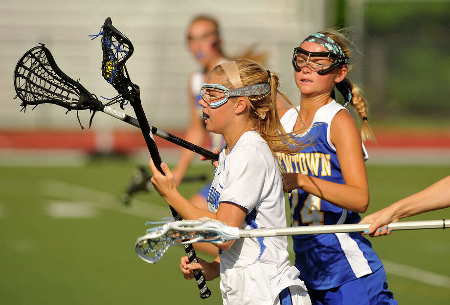 Darien's Lillian Gregory runs the ball up field while under pressure from Newtown's Kristie Voswinkel during their CIAC Class L quarterfinal game at Darien High School in Darien, Conn., on Thursday, June 5, 2014. Darien won 20-5. Photo: Jason Rearick / Stamford Advocate