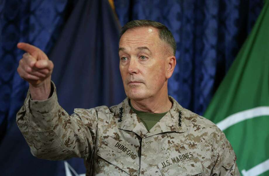 Top U.S. and coalition commander in Afghanistan, Gen. Joseph Dunford, points during a news conference at the ISAF Headquarters in Kabul, Afghanistan, Wednesday, May 28, 2014. Gen. Dunford says that President Barack Obama's decision to keep about 10,000 American troops in the country past 2014 has eliminated any uncertainty Afghans may have had about America's commitment. Gen. Joseph Dunford told reporters Wednesday the decision will allow an advisory force of 9,800 troops to remain in the country to finish training and equipping Afghan security forces. (AP Photo/Massoud Hossaini) Photo: Massoud Hossaini, STF / AP