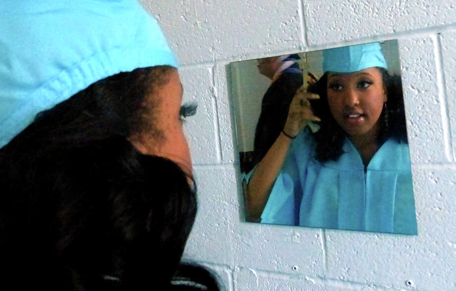 Ronique McDonald checks herself in the mirror before the start of Kolbe Cathedral's Class of 2014 Commencement Exercises at St. Augustine Cathedral in Bridgeport, Conn. on Thursday June 5, 2014. Photo: Christian Abraham / Connecticut Post