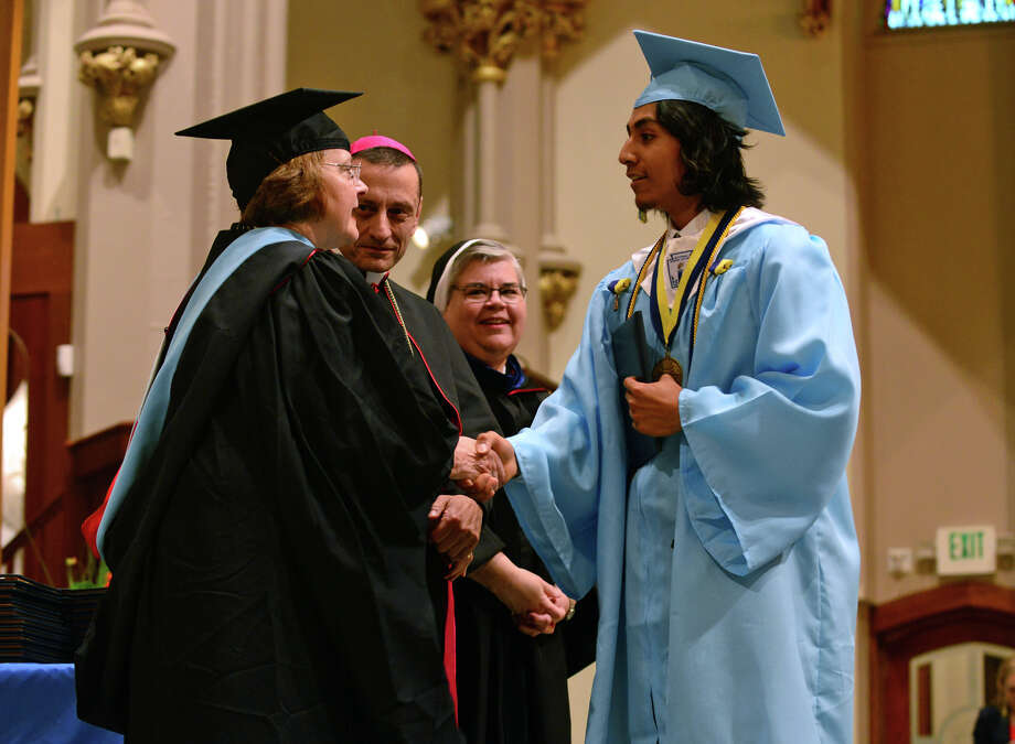 Graduate Eric Cruz receives his diploma, during Kolbe Cathedral's Class of 2014 Commencement Exercises at St. Augustine Cathedral in Bridgeport, Conn. on Thursday June 5, 2014. Photo: Christian Abraham / Connecticut Post