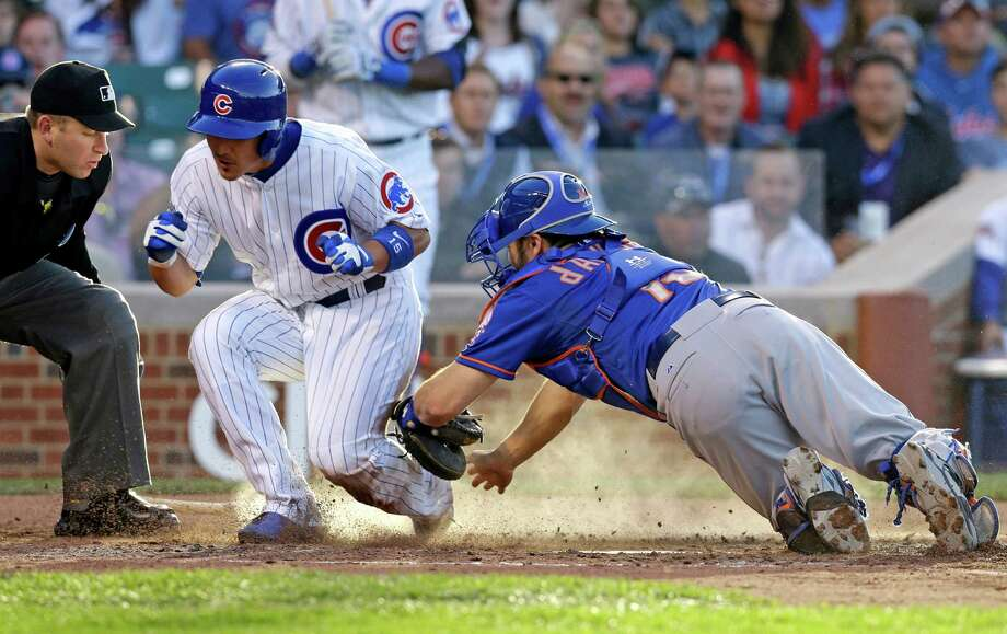Chicago Cubs' Darwin Barney, center, scores past New York Mets catcher Travis d'Arnaud as home plate umpire Clint Fagan, left, looks on during the fourth inning of a baseball game in Chicago, Thursday, June 5, 2014. (AP Photo/Nam Y. Huh) ORG XMIT: CXC110 Photo: Nam Y. Huh / AP