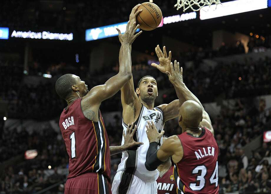 Tim Duncan shoots over Miami's Chris Bosh and Ray Allen during the first half. Duncan led the Spurs with 21 points and 10 boards in the opener. Photo: Michael Laughlin, McClatchy-Tribune News Service