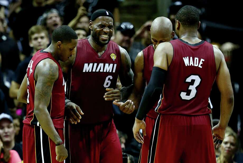 The Heat's LeBron James, center, suffers cramps late in the game Thursday night. A faulty air-conditioning system contributed to a steamy AT&T Center. Photo: Andy Lyons, Staff / 2014 Getty Images