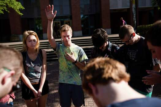 Following the lift of a lockdown in the wake of a school shooting, Caleb Gustin, 19, center, leads Seattle Pacific University students in prayer together Thursday, June 5, 2014, on the campus of Seattle Pacific University in Seattle, Wash. A gunman fatally wounded one young man and seriously injured a 20-year-old woman before being disarmed by a student worker at the small college. Three men and one woman were injured in the shooting, which started at 3:25 p.m. on SPU's Queen Anne neighborhood campus. One of the victims, a man in his 20s, died after being rushed to a hospital. Photo: JORDAN STEAD, SEATTLEPI.COM / SEATTLEPI.COM
