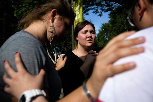 Following the lift of a lockdown in the wake of a school shooting, Seattle Pacific University students pray together Thursday, June 5, 2014, on the campus of Seattle Pacific University in Seattle, Wash. A gunman fatally wounded one young man and seriously injured a 20-year-old woman before being disarmed by a student worker at the small college. Three men and one woman were injured in the shooting, which started at 3:25 p.m. on SPU's Queen Anne neighborhood campus. One of the victims, a man in his 20s, died after being rushed to a hospital. Photo: JORDAN STEAD, SEATTLEPI.COM / SEATTLEPI.COM