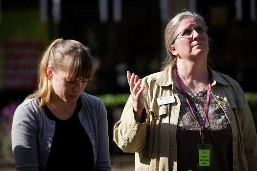 Following the lift of a lockdown in the wake of a school shooting, Seattle Pacific University faculty member Deb Nondorf, right, prays alongside students Thursday, June 5, 2014, on the campus of Seattle Pacific University in Seattle, Wash. A gunman fatally wounded one young man and seriously injured a 20-year-old woman before being disarmed by a student worker at the small college. Three men and one woman were injured in the shooting, which started at 3:25 p.m. on SPU's Queen Anne neighborhood campus. One of the victims, a man in his 20s, died after being rushed to a hospital. Photo: JORDAN STEAD, SEATTLEPI.COM / SEATTLEPI.COM