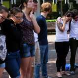 Following the lift of a lockdown in the wake of a school shooting, Seattle Pacific University students pray together Thursday, June 5, 2014, on the campus of Seattle Pacific University in Seattle, Wash. A gunman fatally wounded one young man and seriously injured a 20-year-old woman before being disarmed by a student worker at the small college. Three men and one woman were injured in the shooting, which started at 3:25 p.m. on SPU's Queen Anne neighborhood campus. One of the victims, a man in his 20s, died after being rushed to a hospital.
